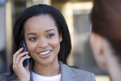 Businesswoman using mobile phone, outdoors, smiling, close-up (differential focus) Royalty Free Stock Images