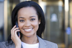 Businesswoman using mobile phone, outdoors, smiling, close-up, front view, portrait Royalty Free Stock Photo