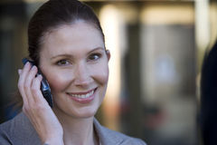 Businesswoman using mobile phone, outdoors, smiling, close-up, portrait Stock Photography