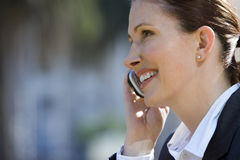 Businesswoman using mobile phone, outdoors, smiling, side view, close-up Stock Image
