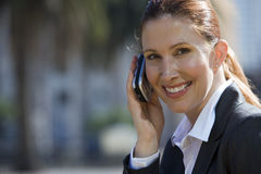 Businesswoman using mobile phone, outdoors, smiling, side view, portrait Stock Images
