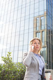Businesswoman using mobile phone outside office building Stock Photo