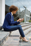 Businesswoman using mobile phone in the premises. Businesswoman using mobile phone in the office premises Stock Photo