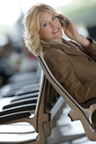 Businesswoman using mobile phone, smiling, side view, portrait (tilt) Royalty Free Stock Image