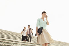 Businesswoman Using Mobile Phone On Steps With Colleagues In Bac Stock Photo