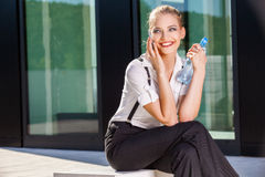 Businesswoman using mobile phone on street against building Stock Photography