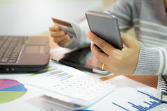Businesswoman using mobile phone to online payment by credit car. D with marketing information graph in office Stock Images