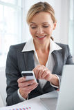 Businesswoman Using Mobile Phone To Send Text Message In Office Stock Photos