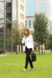 Businesswoman using mobile phone while walking on street Royalty Free Stock Photos