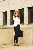Businesswoman using mobile phone while walking on street Royalty Free Stock Photography