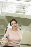 Businesswoman Using Mobile Phone While Writing On Notepad Stock Image