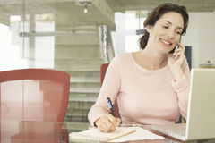 Businesswoman Using Mobile Phone While Writing On Notepad stock photos