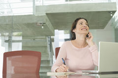 Businesswoman Using Mobile Phone While Writing On Notepad Royalty Free Stock Image