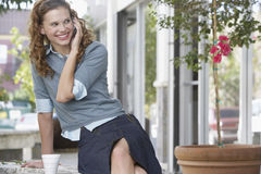 Businesswoman Using Mobilephone While Sitting By Potted Plant Royalty Free Stock Photo