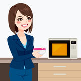 Businesswoman Using Office Kitchen Microwave. Beautiful brunette businesswoman using microwave to heat homemade food on business office kitchen Royalty Free Stock Photo
