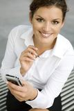 Businesswoman using palmtop. Young woman using palmtop, outdoors Royalty Free Stock Photo