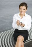 Businesswoman using palmtop. Young woman using palmtop, outdoors Royalty Free Stock Image