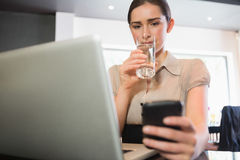 Businesswoman using phone in a cafe Stock Photos