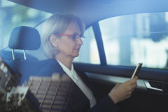 Businesswoman using phone in car Stock Images