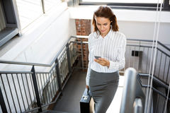 Businesswoman using phone and climbing staircase Royalty Free Stock Images