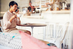 Businesswoman using phone in a coffee shop Stock Image