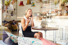 Businesswoman using phone in a coffee shop Stock Photo