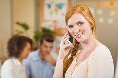 Businesswoman using phone while colleagues working on laptop Royalty Free Stock Photography