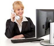 Businesswoman using phone and computer Stock Image