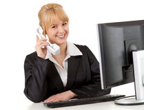 Businesswoman using phone and computer Stock Images