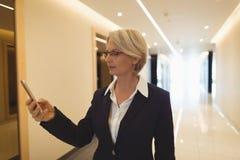 Businesswoman using phone in corridor Stock Photography