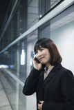Businesswoman using the phone by a glass wall, Beijing Royalty Free Stock Images