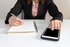 Businesswoman using phone with notebook and pen in the office. Royalty Free Stock Image