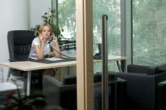 Businesswoman using phone at office Stock Images