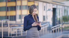 Businesswoman using phone at office building. Young pretty confident female office worker standing and browsing. Young pretty confident female office worker stock video footage