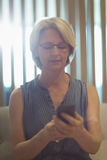Businesswoman using phone in office Stock Photography