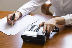 Businesswoman using phone, taking notes at office desk Stock Images