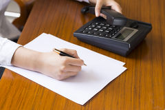 Businesswoman using phone, taking notes at office desk Stock Photo