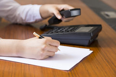 Businesswoman using phone, taking notes at office desk Royalty Free Stock Photo