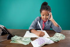Businesswoman using phone while writing on book by paper currency Stock Photography