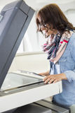 Businesswoman using photocopier in creative office Royalty Free Stock Photo