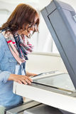Businesswoman using photocopier in creative office Royalty Free Stock Photography