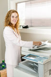 Businesswoman using photocopier in office Royalty Free Stock Photography