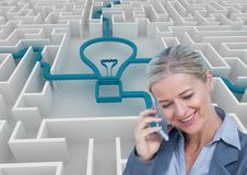 Businesswoman using smart phone against light bulb connected in maze. Digital composite of Businesswoman using smart phone against light bulb connected in maze Royalty Free Stock Photos