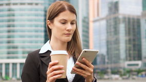 Businesswoman using smart phone in city downtown, professional female browsing chatting reading news. Young successful businesswoman in suit using smart phone in stock footage