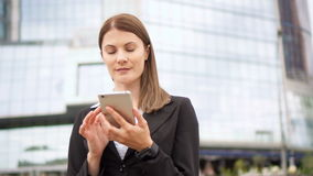 Businesswoman using smart phone in city downtown, professional female browsing chatting reading news. Young successful businesswoman in suit using smart phone in stock video footage