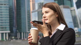 Businesswoman using smart phone in city, professional female employer talking with business partner. Young successful businesswoman in suit using smart phone in stock video footage