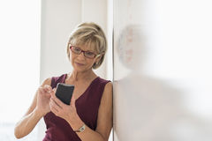 Businesswoman Using Smart Phone While Leaning On Whiteboard Royalty Free Stock Photos