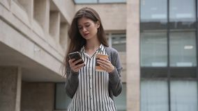 Businesswoman using smart phone while standing with coffee.  stock footage