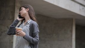 Businesswoman using smart phone while walking with coffee.  stock video footage