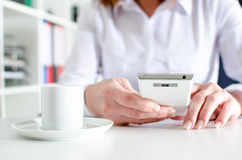 Businesswoman using a smartphone during coffee break Stock Image